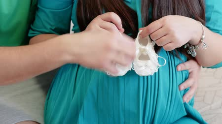 baptism : Future parents holds booties for newborn. Maternity concept