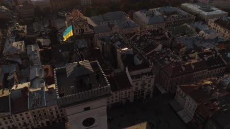 Украина : Aerial shot of Lviv town hall with waving yellow-blue flag. Cultural center of Ukraine