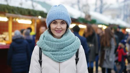 ona : Portrait of a young woman smiling outdoors. She wears blue hat and scarf