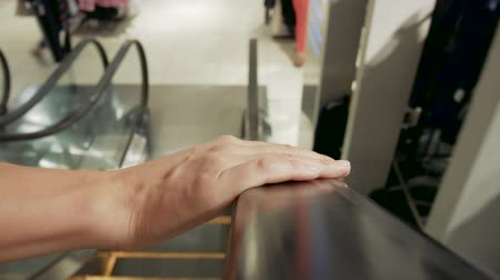 consumo : Womans hand on escalator handrail. Girl goes to a clothing store for a shopping. Consumption era concept Vídeos