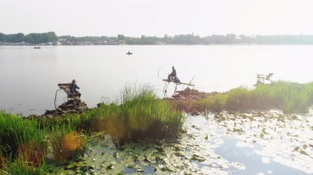 Деятельность выходные : Remarkable ssunset with fishermen by the river. Aerial footage. Hobby for the elderly. Pastime retired