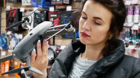haklar : Young girl in the electronics store chooses gray drone. She carefully examines the quadcopter before buying. On the background of gadgets and accessories. Gender equality and womens rights concept
