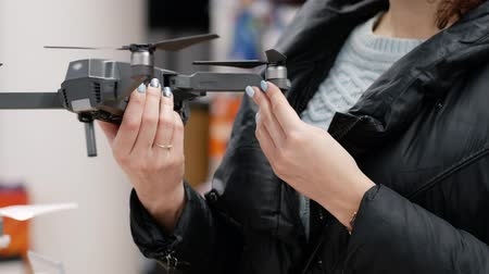propeller toy : Woman in the electronics store chooses gray drone. She carefully examines the quadcopter before buying. On the background of gadgets and accessories. Gender equality and womens rights concept Stock Footage