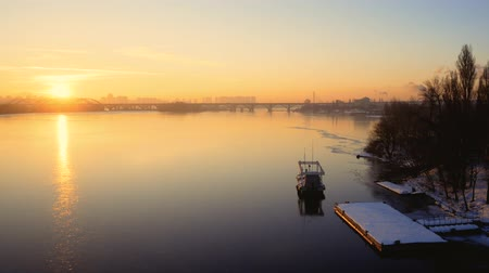 восхитительный : Delightful morning landscape. Lonely motorboat on a frozen river at dawn. Bridge on the background