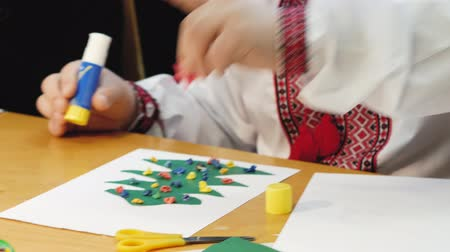 preciso : Boy with Down syndrome sticks a star to the Christmas tree on paper. Rehabilitation for special children concept