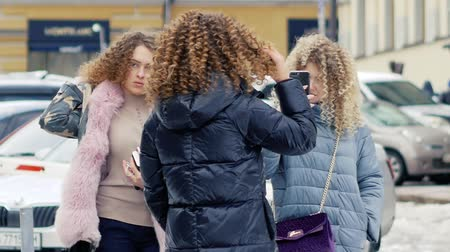 twin : Curly girls are photographed by a smartphone on the avenue. Young women of fashion have fun. Ukrainian women