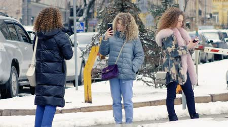 dvojčata : Three curly girls are photographed by a smartphone on the avenue. Young women of fashion have fun. Ukrainian women