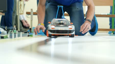 školák : Kyiv, Ukraine - February 22, 2019: A young guy starts a robotic car on a special track that goes straight to the camera. Classes in robotics for younger students