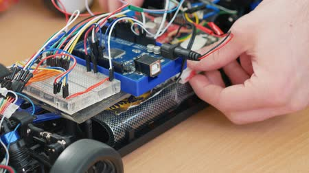 obstacles : A young engineer assembles a robotic machine. Close up. Classes in robotics for younger students Stock Footage