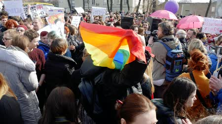 direitos : Kyiv, Ukraine - March, 2019: Man holds LGBT flag at womens march in Kyiv