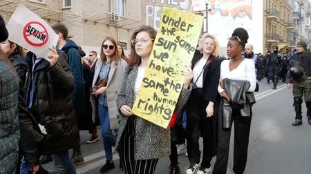 равный : Kyiv, Ukraine - March, 2019: Mixed race girls holds signs at womens march in Kyiv