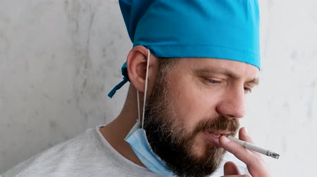 smettere di fumare : Depressed doctor after a difficult operation removes the mask and starts to smoke. Close up