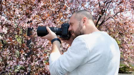 Cute photographer in the process of shooting. A man takes a blooming sakura on a digital camera