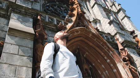 Bearded tourist views the church in the Gothic style. Travel concept Vídeos