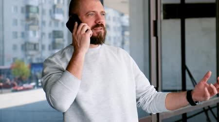 Handsome man with a beard talking on the phone and actively gesticulating with his hands. Close up