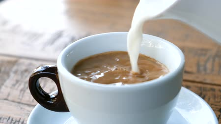 latte macchiato : Milk is poured into a cup of coffee. Coffee with milk in the summer cafe. Close up Stock Footage