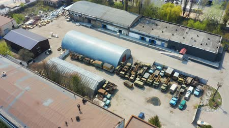 Birds eye view of an old storage rooms with broken cars and trucks. Aerial footage