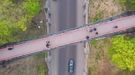 Flying over the pedestrian bridge in the park on which people walk. Spring outside. View from above