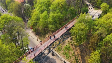 Flying over the pedestrian bridge over the road, which people walk and pass a cyclist. Aerial footage of the bridge in the park. Spring Park in the city