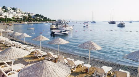parasol : Time lapse on the coast of the resort town of Bodrum, Turkey. Umbrellas and sun beds on the beach. Yachts and boats bobbing on the waves early in the morning. Travel concept Stock Footage