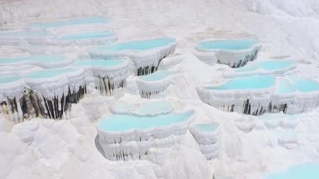Pan view of travertines in Pamukkale, Turkey. Thermal springs located on white limestone terraces. Aerial footage 4k