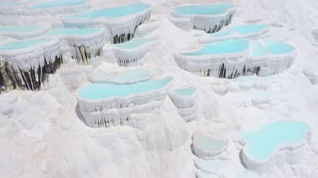 Natural travertines in Pamukkale, Turkey. Thermal springs located on white limestone terraces. Aerial footage 4k