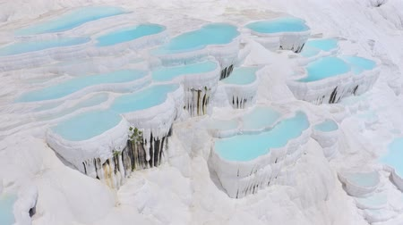 Tilt shift of camera from travertines to tourists in Pamukkale, Turkey. Aerial footage 4k