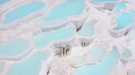 Flying over the travertines in Pamukkale, Turkey. White limestone mineral formations. Aerial footage 4k