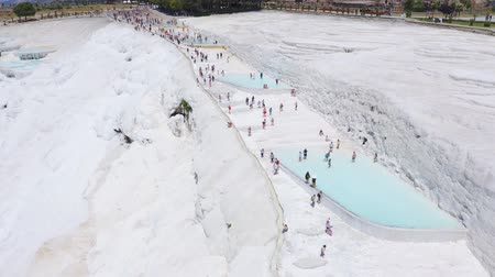 Crowds of tourists on the terraces of white limestone. Pamukkale, Turkey. Aerial footage 4k