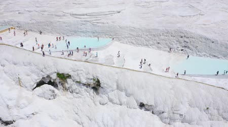 havza : Panoramic fly over Pamukkale mountain with tourists walking near travertines. Denizli, Turkey. Aerial 4k Stok Video