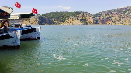 deep sea exploration : Tourist boats with the Turkish flag are moored on the bank of the Dalyan River. Habitat of the turtle Caretta caretta. Tourists sketched crabs in the water to attract turtles 4k Stock Footage