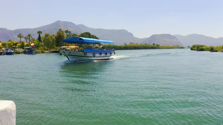 Amazing landscape on the river Dalyan, Turkey. Sailing past the tourist boat. Reeds and mountains in the background 4k