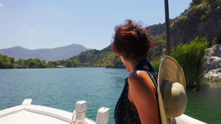 A brunette in a hat sailing in a white boat along the Dalyan River and enjoys the mountain landscape. Medium plan steadicam 4k
