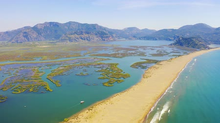 separação : Aerial survay over the river Dalyan. Iztuzu Sand Spit separates the river and the sea. Tourist boat sailing on the river. Birds eye view 4k