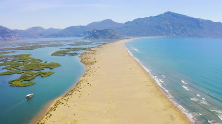 aegean sea : Aerial survay over Iztuzu Sand Spit separates the river and the sea. Tourist boat sailing over the river. Birds eye view 4k