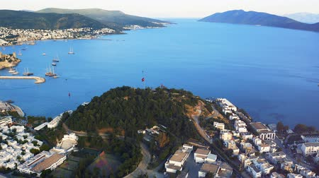 Aerial shot orbiting around hill with red turkish flag on top of it in resort town Bodrum, Turkey. Welcome to Turkey concept 4k