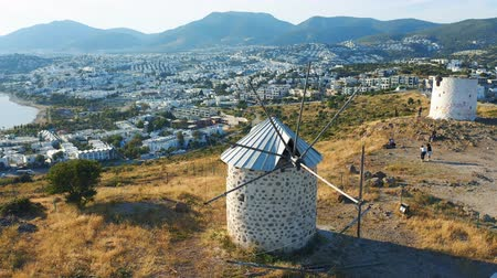 zbourán : Old windmills at sunset in Bodrum, Turkey. Tourists taking photos against the landscape. Welcome to Turkey concept. Aerial 4k