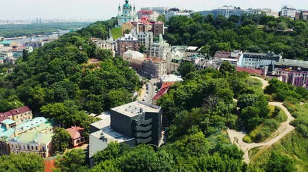 Slow rising shot over bushy hill revealing Andrews descent and Andrews Church in Kiev. Famous place in Kyiv. Aerial footage 4k Vídeos