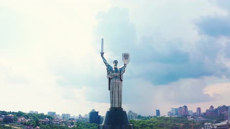 Soviet-era monumental statue Motherland with heavy clouds on background. Mother with a shield and sword in the capital of Ukraine, Kiev. Overall plan 4k