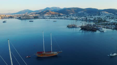 Fly over yachts moored in Bodrum bay at the sunset. Mountains on background 4k