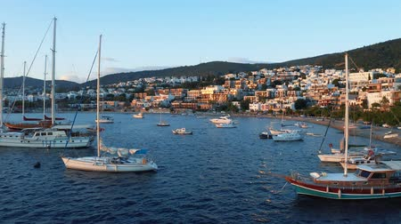 Yachts moored in the bay during the sunset. Resort town Bodrum (Halicarnassus) with white houses on background 4k