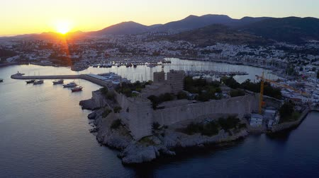 aegean sea : Anceint Castle of St. Peter at the sunset. Yachts moored in the bay of resort town in mediterranean sea 4k
