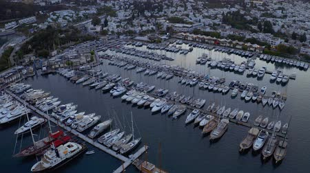 Aerial fly over boats and yachts moored in port at the sunset. View from above 4k