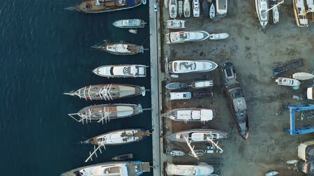 Yachts and boats moored at the dock shipyard. Aerial view from above 4k