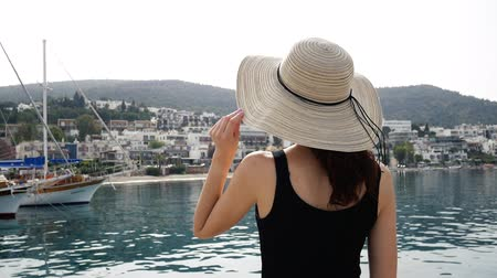 bodrum : The girl in a round hat admires the beauty of the port landscape. The resort town of Bodrum with white houses in the Greek style. Close up 4k