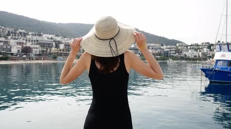 bodrum : The girl in a round hat admires the beauty of the port landscape. The resort town of Bodrum with white houses in the Greek style 4k Stock Footage