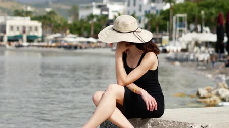 bodrum : Sad pretty woman with black dress and round hat sitting in the port and dreaming 4k Stock Footage
