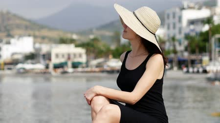 bodrum : Beautiful girl in a round summer hat sits on the background of yachts and boats moored in the port of the resort town 4k Stock Footage