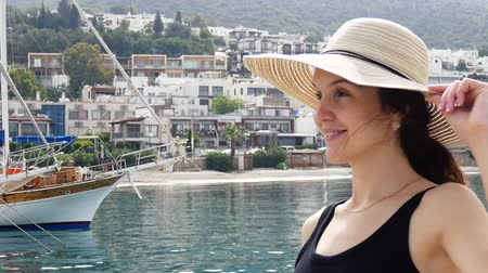 bodrum : Beautiful girl in a round summer hat enjoys views of the resort town. Yachts and boats moored in the port in the background. Close up