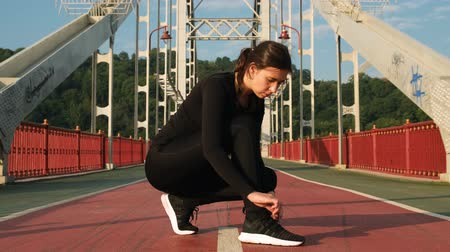 cipőfűző : Attractive woman tying shoelace on sneakers on city bridge and starting to run. Female athlete ties running shoes before training 4k Stock mozgókép